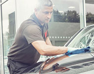 Small image of a man cleaning a used car.
